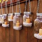 kerzen in an der Holzwand ausgehängten Gläsern