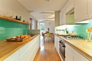 kleine Küche in weiß mit Holztheken und Glas