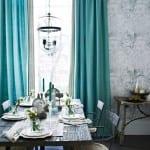 moderne Essyimmereinrichtung mit Holztisch und blaue Gardinen