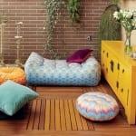 terrasse mit Holzplatten und dekorativen Sitzkissen-gelbe Kommode-terrasse mit Ziegelwand