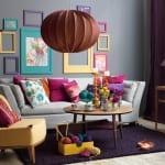 Wandgestaltung mit farbigen bildrahmen- sofa grau- kissen pink-teppich violett