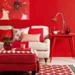 wohnzimmer mit wandfarbe rot und sofa weiß mit roten kissen-polsterhocker rot mit qarierter Sofadecke-holztisch rot mit roter tischlampe