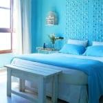 farbgestaltung schlafzimmer mit blauen wänden und weißem bett mit blauer bettdecke-wanddeko idee mit glassteinen-weiße Holzbank