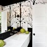 modernes badezimmer mit weißem waschtisch und schwarzen fliesen-wandgestaltung mit schwarzem wandtatoo baum-badezimmerspiegel