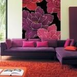 modernes wohnzimmer mit lila sofa und orangem polsterhocker-wandgestaltung mit schwarzem bild und blumen in rosa und violett