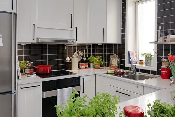 kleine küche mit schwarzen wandfliesen und weißen kücheschränken ...