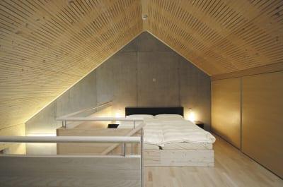 luxus schlafzimmer mit dachschräge und akustikpaneelen aus holz