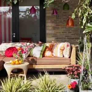 das kleine wohnzimmer auf die terrasse mit terrassenüberdachung und rattansofa mit couchtisch rund aus rattan