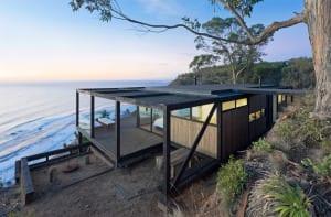 ein Traumhaus aus Holz mit große Holzterrasse und Flachdach