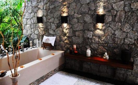 luxus-badezimmer-mit-natursteinwand-und-badewanne-einmauern-im-außenbereich
