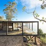 traumhaus am Hang aus holz mit Holzterrasse und Sollarpaneelen