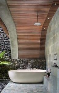 modernes badezimmer im garten mit steinmauer und holzüberdachung