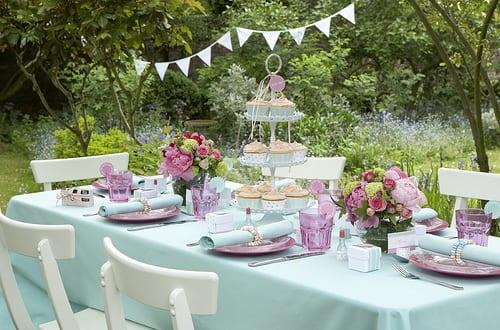 tisch eindecken mit tischdeko in hellblau und rosafarbigen teller als deko idee für gartenparty