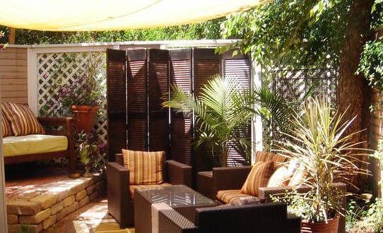 wohnzimmer desing im garten mit rattanmöbeln braun und terrassenbeschatung mit sonnensegel