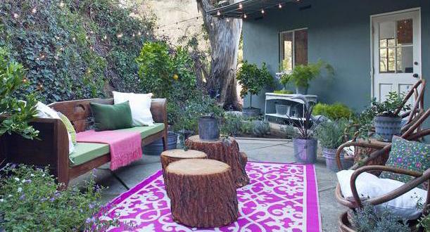 wohnzimmer im garten einrichten mit teppich in lila und weiß und runde couchtische aus holz