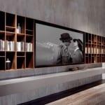 luxus wohnzimmer interior in beton optik mit wandfarbe grau und wandregal holz mit TV Wandpaneel
