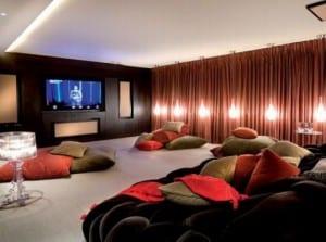 wohnidee luxus wohnzimmer als Medeiaraum mit roten vorhängen und modernes sofa schwarz