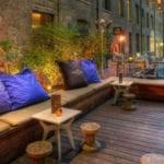 holzterrasse einrichten als schickes Cafe mit Holzsitzbänken und runden holzhockern