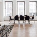 luxuriöses Loft Interieur Design mit Parkett, modernem Holzesstisch mit schwarzen Stühlen, modernem Sofa grau mit holzcouchtisch auf gemustertem teppich braun, stehelampe holz und schiebefenstern