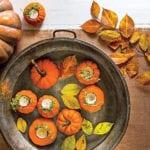 tisch eindecken und rustikal dekorieren mit diy Herbst Tischdeko _teelichthalter aus orangen kürbissen und herbstblätter in metallschale