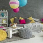 kreative farbgestaltung kinderzimmer mit wandfarbe grau, weißem bodenbelag, sofa mit grauen decken und gelben kissen, couchtisch aus paletten mit gestrickten polsterhockern und pflanzen in holzkisten