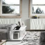 modernes wohnzimmer interieur in weiß und grau mit polstersofa grau, bücherregal-beistelltisch , holzpendellampen über holzcouchtisch und moderne heizkörperverkleidung weiß unter holzfensterrahmen