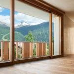 gemütliche und moderne raumgestaltung mit parkettboden, holz-alu-fenster und hebeschiebetür mit romantischem blick auf die berge