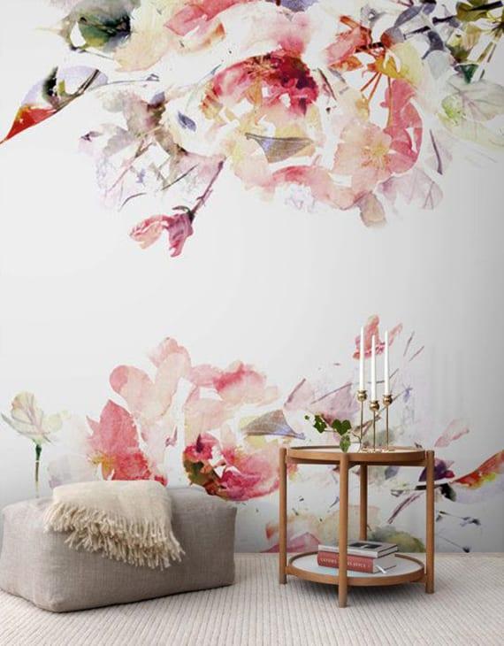 coole wandgestaltung wohnzimmer mit blumen in wasserfarbe, rundem beistelltisch holz und polsterhocker grau mit weißer decke