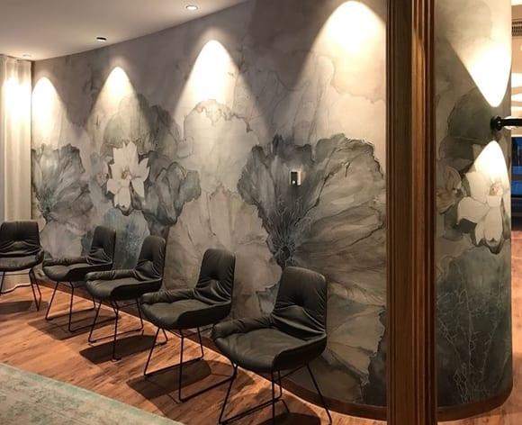 coole raumgestaltung wartezimmer mit schicker wandgestaltung gerundeter wand mit blumen-wandtapete in grau und scheinwerferlichtern