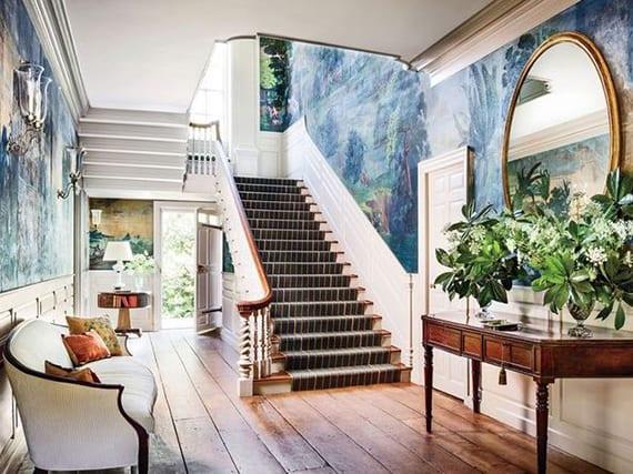 eingangsbereich mit treppe vom haus im klassischen stil kreativ gestalten mit weißer holzwandverkleidung, antiken holzmöbeln, wandtapete als akzent im blau und rundem spigel im goldrahmen