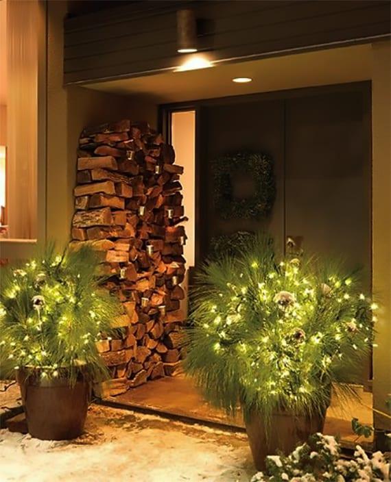 moderner hauseingang mit zweiflügeltür schwarz und Fenster elegant dekorieren zu weihnachten mit kaminhölzern und tannengrün mit silbernen weihnachtskugeln und lampen in runden blumenkübeln