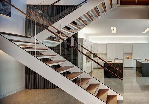 luxus wohnzimmer mit offener küche weiß, kochinsel, raumtrennung mit gardine grau, innentreppe weiß mit treppenstufen holz