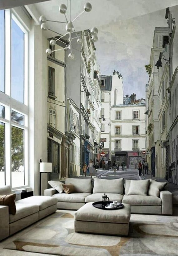 wohnzimmer mit hoher decke gemütlich gestalten in beige mit 3er sofa, hocker-couchtisch, teppich mit geometrieformen,moderner pendellampe in silber und wandtapete stadtstraße,