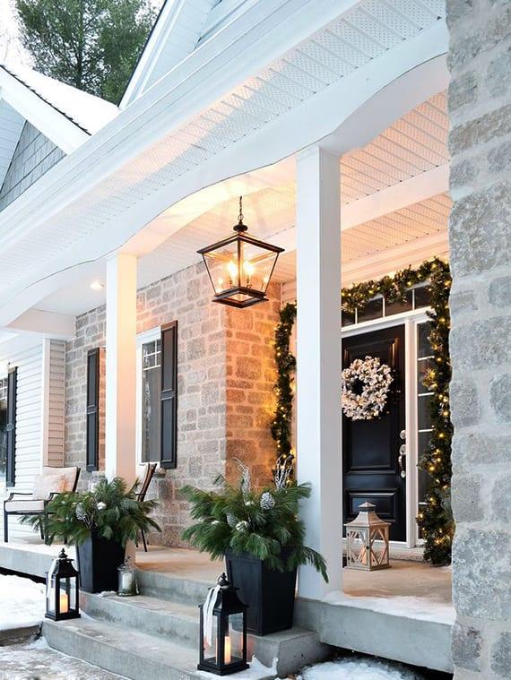 modernes haus weiß mit veranda und schwarzer haustür festlich zu weihnachten dekorieren mit leuchtender girlande aus tannengrün, höngelampe-laterne, nadelbaumzweigen in schwarzen blumenkübeln und schwarzen laternen