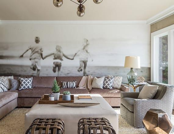 wand im wohnzimmer originell gestalten mit einem Fotodruck, ecksofa lila, rechteckigem hocker wei0, weidenhocker metall, beistelltisch kupfer