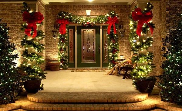 hauseingang weihnachtsdeko mit leuchtenden tannengrün-girlanden und roten schleifen