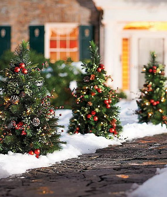 coole outdoor dekoideen für weihnachtsdeko garten mit kleinen weihnachtlich geschmückten christbäumen entlang dem gartenweg
