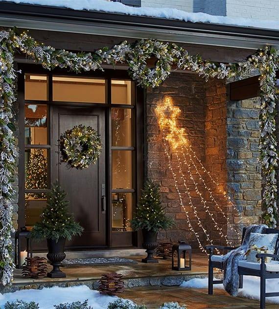 moderner Hauseingang mit Überdachung und Steinveschalung weihnachtlich dekorieren mit verschneiten Tannegrüngirlande und Weihnachtskränzen, schwarzen laternen mit kerzen und kleinen tanenbäumen mit weihnachtsleuchten in schwarzen amphoren