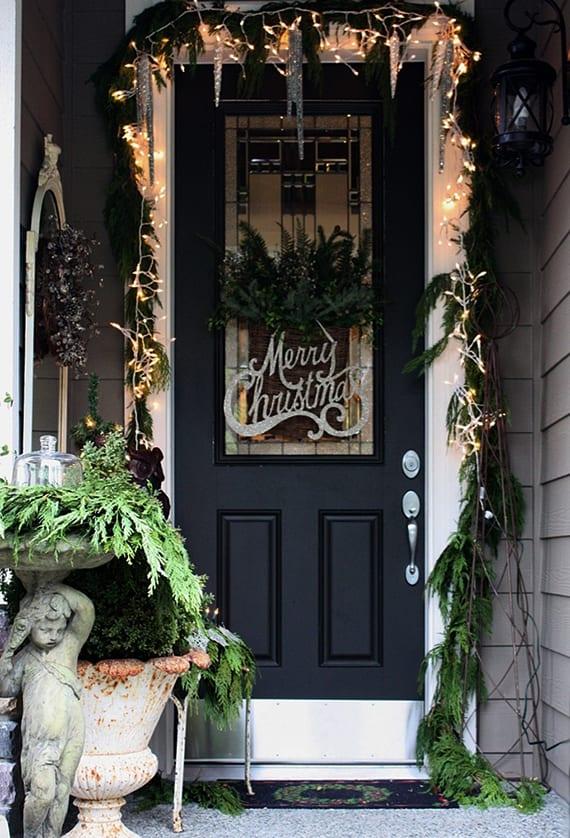 kleiner hauseingang mit grauen holzwänden und schwarzer haustür in weißer türrahmen fröhlich zu weihnachten dekorieren
