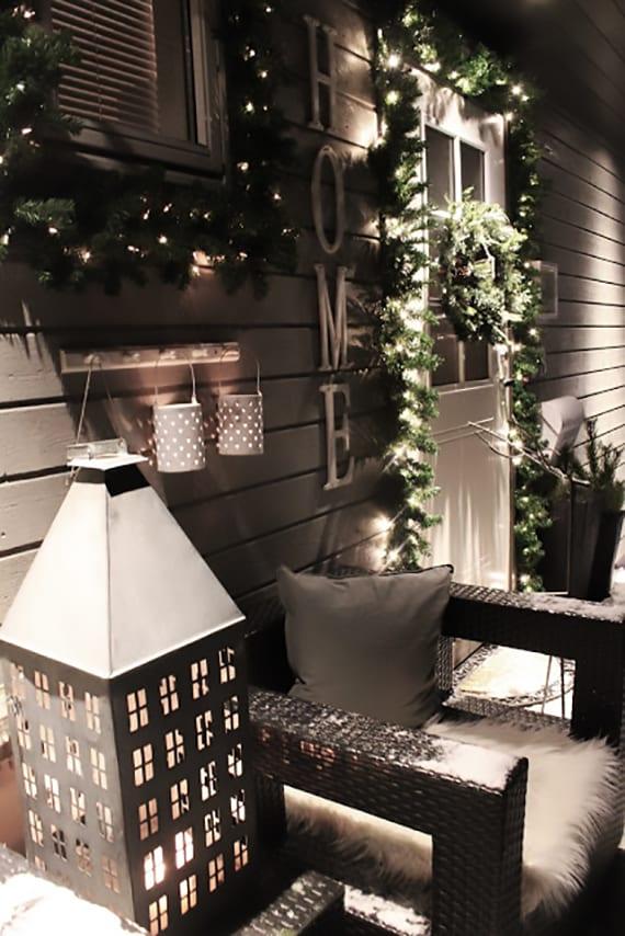 veranda weihnachtlich dekorieren mit einem haus-laterne aus metall, rattan-gartenstühlen mit pelzen, leuchtende weihnachtskränze aus nadelbaumzweigen