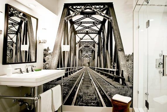 industrielles badezimmer interiur in schwarz und weiß mit badezimmerspiegel im schwarzen spiegelrahmen, stahlrohr waschtisch unterschrank, vintage fototapete