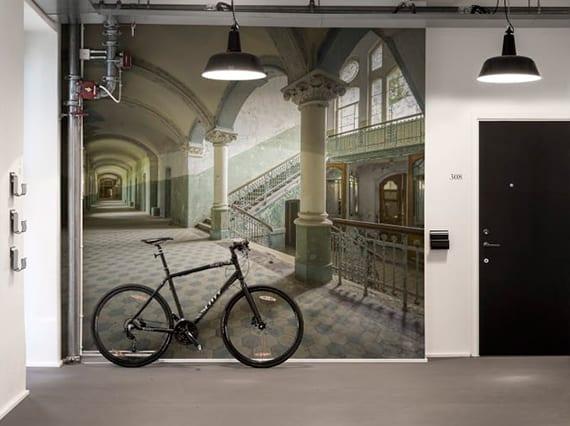 flur modern gestalten mit grauem boden, schwarzer eingangstür, hängelampen schwarz und wandtapete mit treppenraum im barock-gebäude