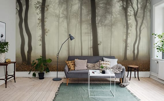 skandinavisches wohnzimmer mit holzboden, sofa grau, teppich grün, rechteckigem couchtisch weiß, stehlampe grau, wandtapete nebel im wald