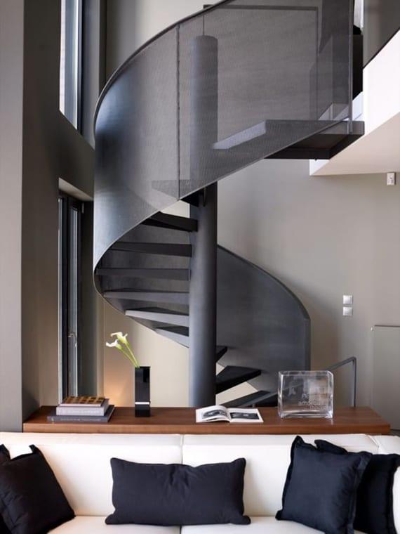 schwarze spindeltreppe mit geländer im wohnzimmer mit offener galerie