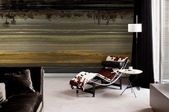modernes wohnzimmer gestalsten mit boden und tv-regal weiß, sofa schwarz, designer ligestuhl aus kuhfell mit rundem beistelltisch und stehlampe, tapete-akzentwand in grau und gold, vorhang schwarz