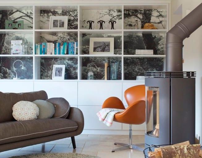 kleines wohnzimmer kreativ gestalten mit sofa grau, drehstuhl orange, rundem kamin schwarz, Regal weiß mit wandregal ohne rückseite