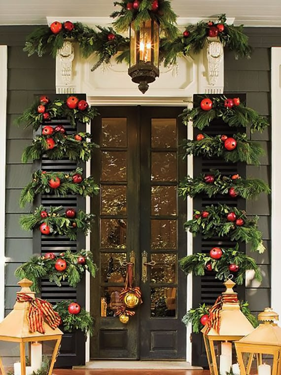 hauseingang mit fenstertürläden kreativ dekorieren zu weihnachten mit nadelbaumzweigen und grantäpfeln