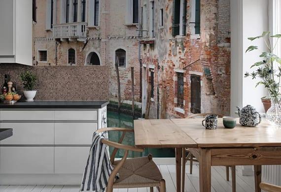 coole gestaltungsidee für weiße küche mit kleinem holzesstisch vor dem fenster mit passender fototapete hinter der küchenarbeitsplatte