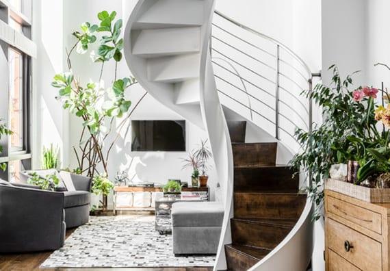 coole wohnzimmer idee mit schmaler wendeltreppe weiß, sessel und hocker grau, sideboard auf rollen, holzregal, deko mit zimmerpflanzen