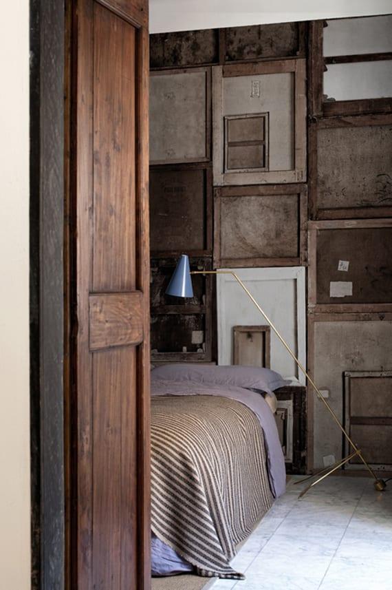 gestaltungsidee für rustikales schlafzimmer mit rustikaler wandgestaltung, vintage stehlampe und bettwäsche lila